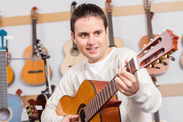 Man playing a guitar in music store