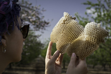 Woman holding honeycomb.