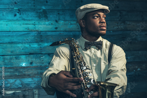 Poster African american jazz musician with saxophone in front of old wo