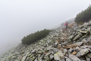Backpacker walking mountain slope in fog. Pirin, Bulgaria.