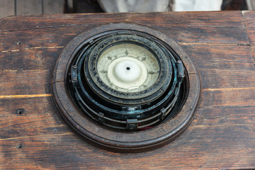 Old ships compass on deck of a tall ship