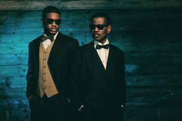 Two vintage african american gangsters in front of old wooden wa