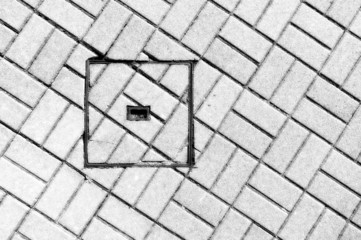 abstraction of sewer manhole on floor with cobblestones
