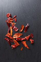Dried chilly / chili flakes on black slate, top view