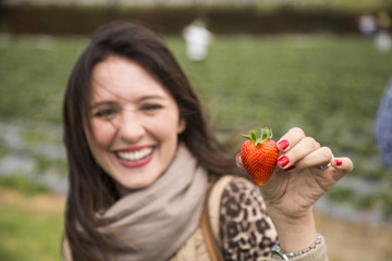 Woman holding a strawberry in her hands.