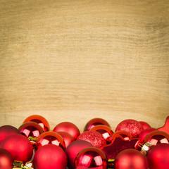 roter christbaumschmuck vor rustikalen hintergrund