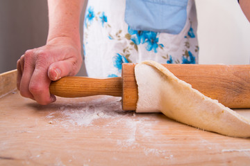Rolling out the dough on a board in the kitchen