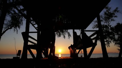 Friends in Summer House on the Beach at Sunset near the Sea.