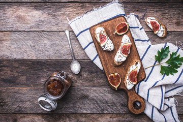 Bruschetta with figs on chopping board in rustic style