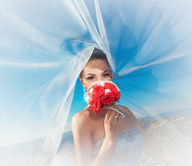 Beautiful bride with veil on wind