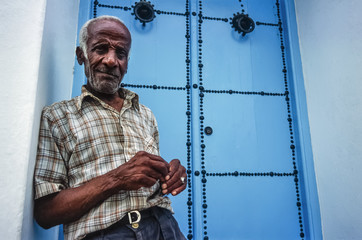 Tunisia, Sidi Bou Said, tunisian man in front of his frontdoor
