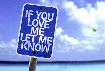 If You Love Me Let me Know sign with a beach on background