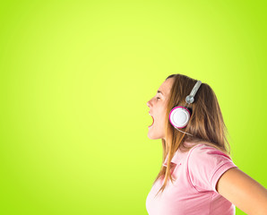 Young blonde girl listening music over green background