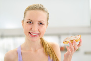 Happy young woman eating toast with chocolate cream