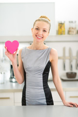 Portrait of happy young housewife showing heart in kitchen