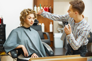 Hairdresser doing hairstyle for young beautiful woman