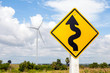 Winding road sign and windmill background in wind farm.