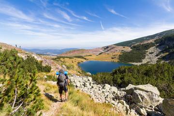 Backpacker walking trail towards mountain lake.