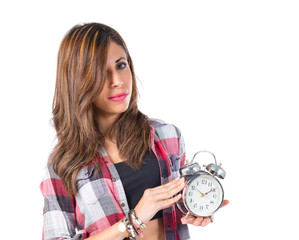 Girl holding a clock over white background