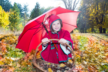 Cute child girl playing with umbrella in leaves in autumn park
