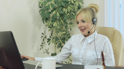 Beautiful blonde in the office with headphones speaks on