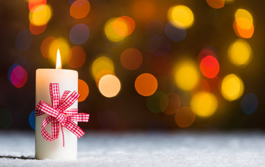Xmass candle in snow, with bokeh background, copy space
