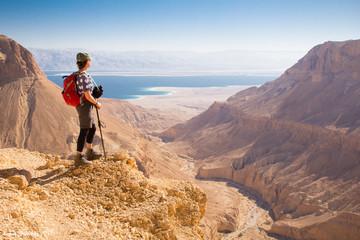 Backpacker woman standing desert mountain edge.