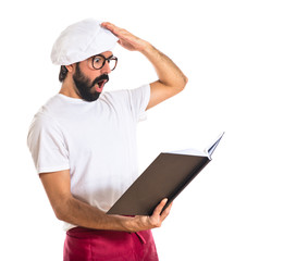 Surprised chef reading book