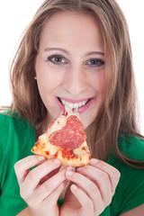 Junge Frau isst glücklich ein Stück Salami Pizza und lacht