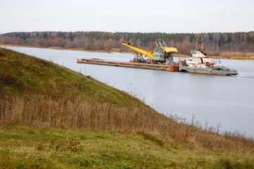 The river tow pushes the barge with a dredge