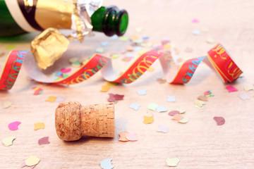 Sektflasche, Korken, Konfetti und Papierschlangen großflächig