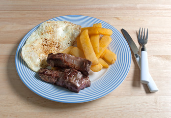 Breakfast meal on blue striped plate with fork and knife