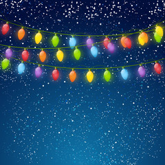 Color Christmas light bulbs on sky background