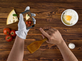 cook chef hands with smartphone and ingredients for food on vint