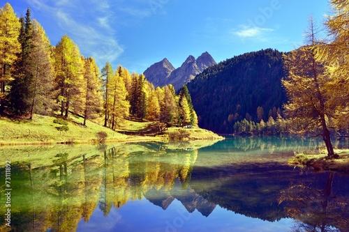 Foto op Canvas Foto van de dag Herbstfarbene Lärchen spiegeln sich im Palpuognasee