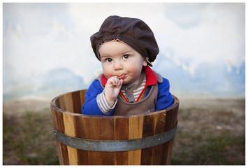 Baby boy in wooden pot