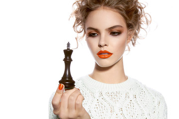 Beautiful woman with evening make-up holding a king chess piece