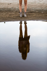 The feet of the woman with casual clothes and her reflection