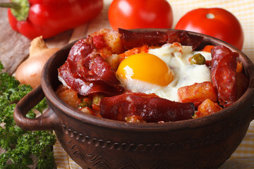 Baked eggs with chorizo and vegetables in the pot. Horizontal