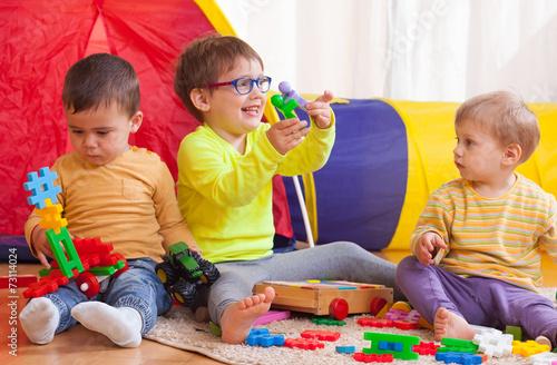 Leinwanddruck Bild children playing together at home