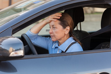 frightened mature woman in   car.