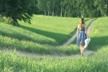 girl walking along the road in a field alone