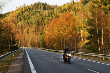 Asphalt road in the autumn landscape with a ride motorcycle