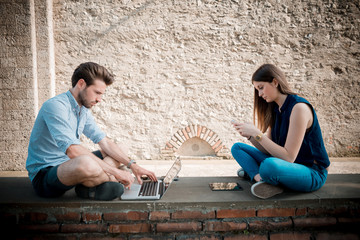 young couple using technology multitasking smarpthone tablet and