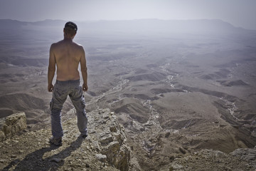 Man standing desert cliff edge