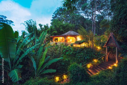 Leinwanddruck Bild Tropical Home in the Jungle at Sunset