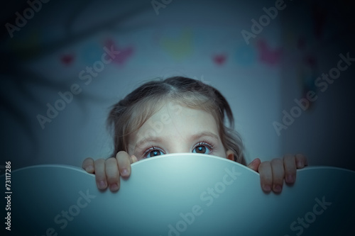scared little girl in her bed - 73117286