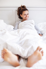 Smiling woman sits in the bed covered with soft blanket .