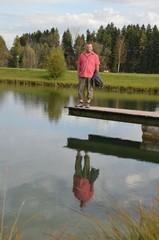 Mann am See auf Bootssteg spiegelt sich