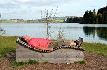 Mann entspannt auf Liege am See
